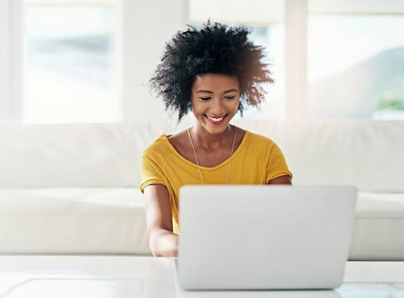 Une jeune femme sur son ordinateur portable dans son salon