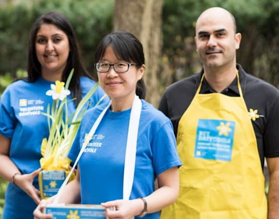 Three young Daffodil volunteers selling pins