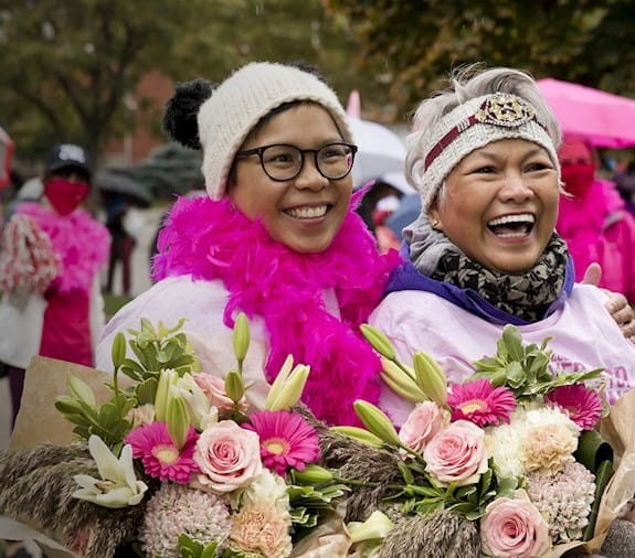 Two women, holding flowers, smiling