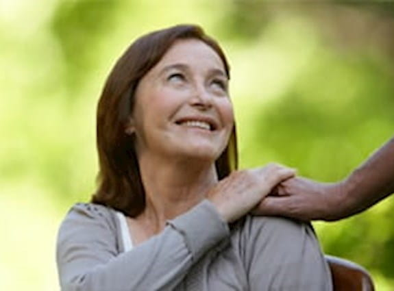 A woman looks back and up at a person who has placed their hand on her shoulder