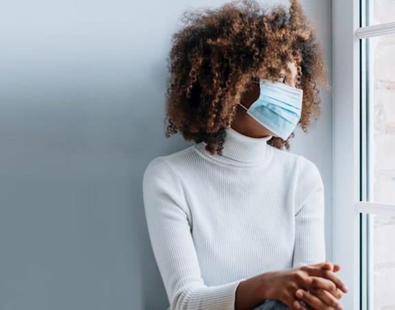 Femme portant un masque regardant par la fenêtre