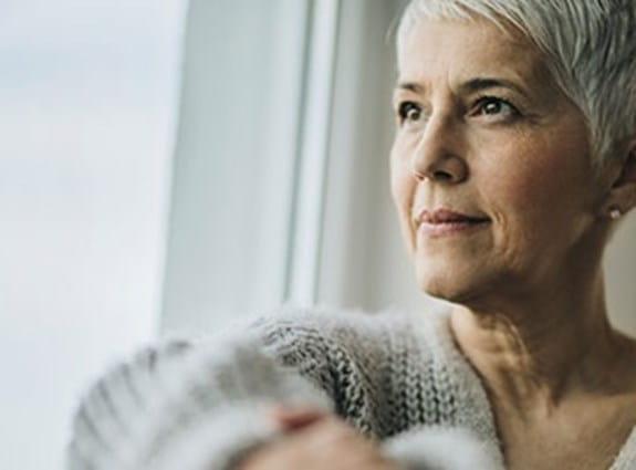Femme assise, regardant par la fenêtre.