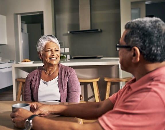 Dame et homme âgés assis à une table et discutant.