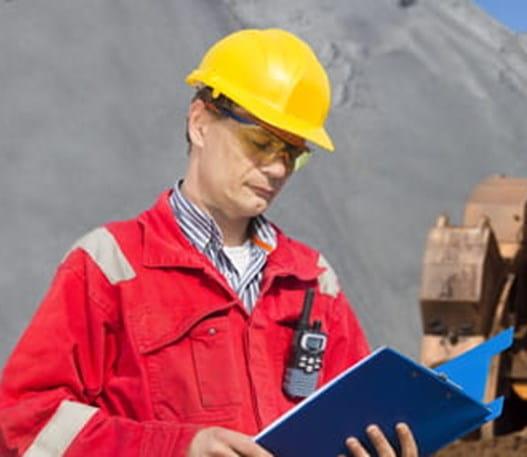Un travailleur extérieur consulte un document sur une planchette sur un chantier de construction