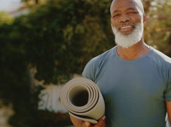 Homme portant un tapis de yoga à dehors