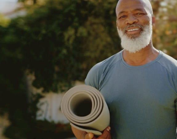Man holding a yoga matt outdoors