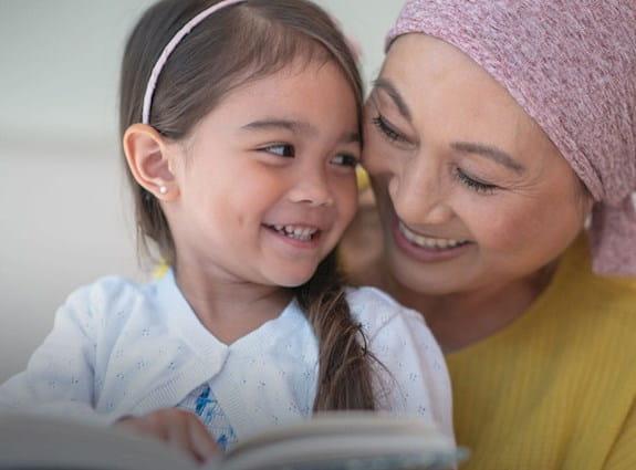 Petite fille faisant la lecture à une dame âgée portant un foulard sur la tête.