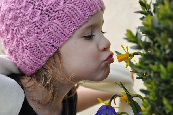 Une petite fille embrassant une jonquille.