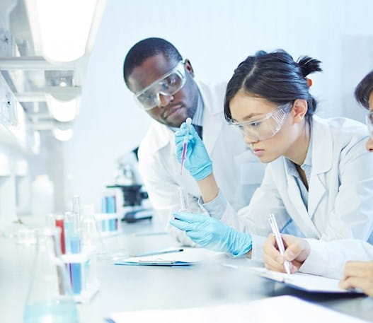 A female researcher in a lab, working with 2 other male researchers.