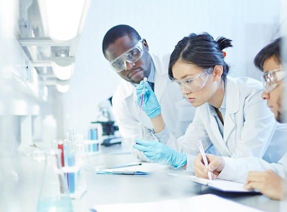 Une chercheuse dans un laboratoire, travaillant avec deux chercheurs