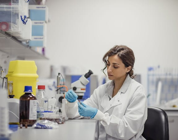 A female researcher conducting experiment at a lab.