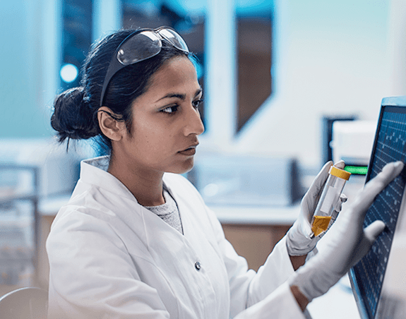A female cancer researcher typing into a touch screen and holding a vial in a lab.