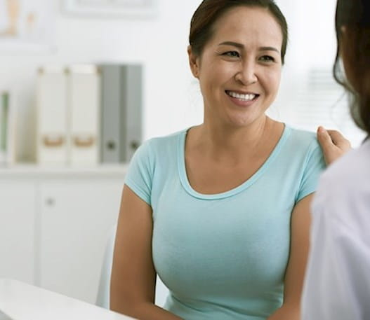 a woman is speaking with her doctor who has placed their hand on her shoulder