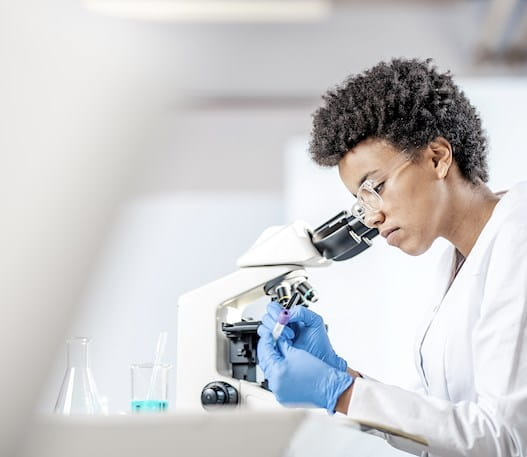 A scientist looking into a microscope.
