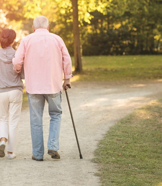 A woman and an elderly man walking with a cane.
