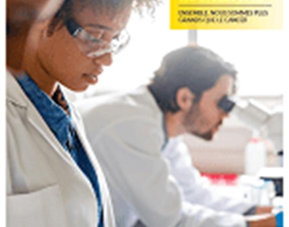 Deux scientifiques au travail à un bureau pendant qu'un troisième regarde dans un microscope.
