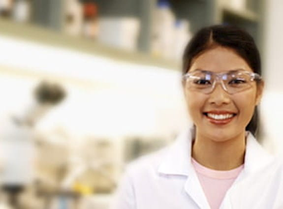 Two cancer researchers wearing lab coats and safety glasses