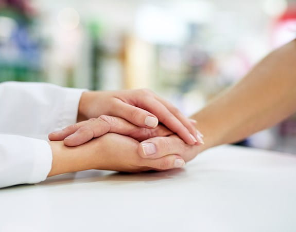 An older persons hand is being embraced by the hands of a younger person
