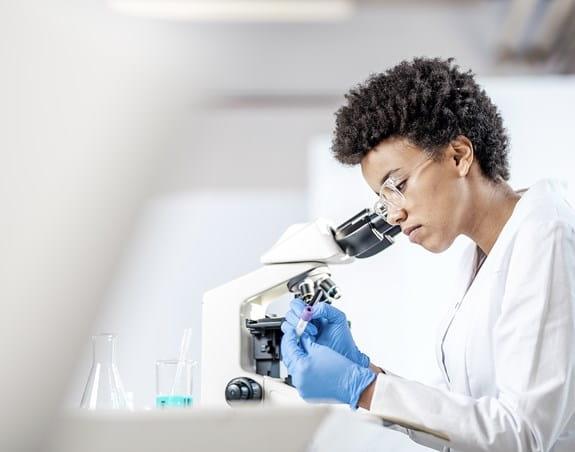 Scientifique assise derrière un microscope, écrivant sur une éprouvette.