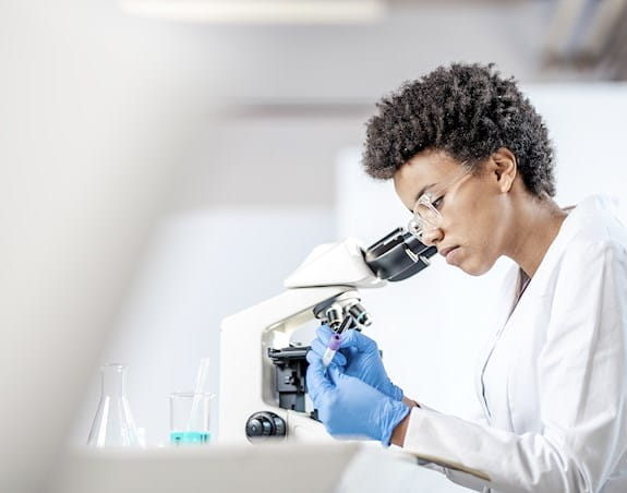 A female scientist is writing on a test tube while sitting behind a microscope