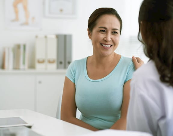 A woman is smiling while having a conversation with her doctor.
