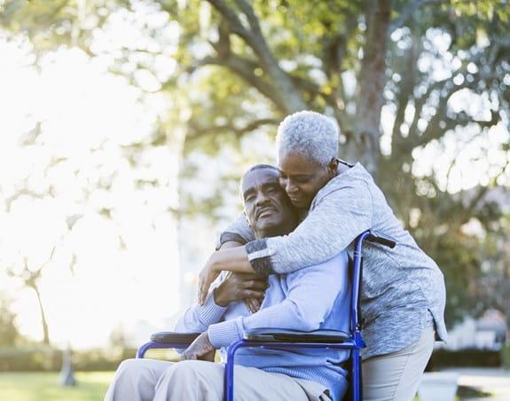 Femme enlaçant un homme installé dans un fauteuil roulant.