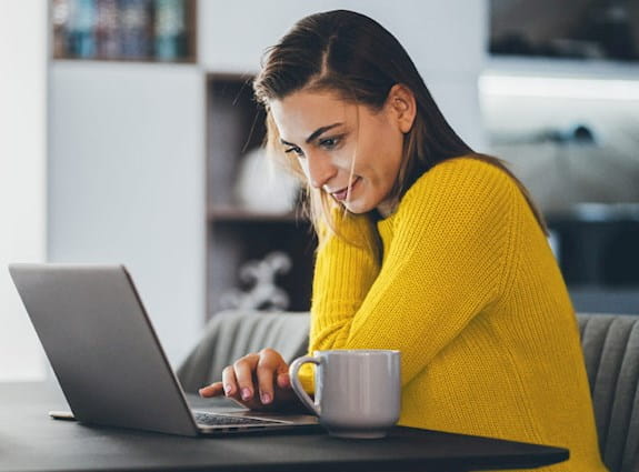 a woman sits at her kitchen table working on her laptop