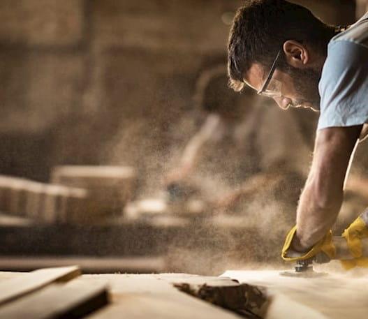 Homme sur un chantier en train de poncer une pièce de bois à l'aide d'un outil électrique.