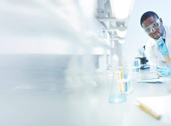 Three scientists work at a desk, one takes notes while another pours liquid into a test tube
