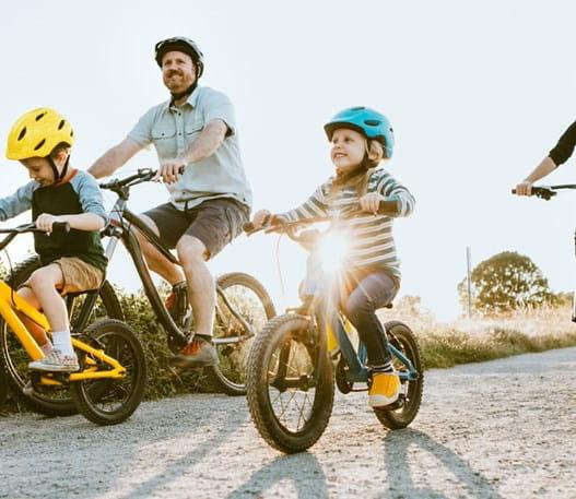 Un père et une mère et leurs deux enfants faisant du vélo sur un chemin