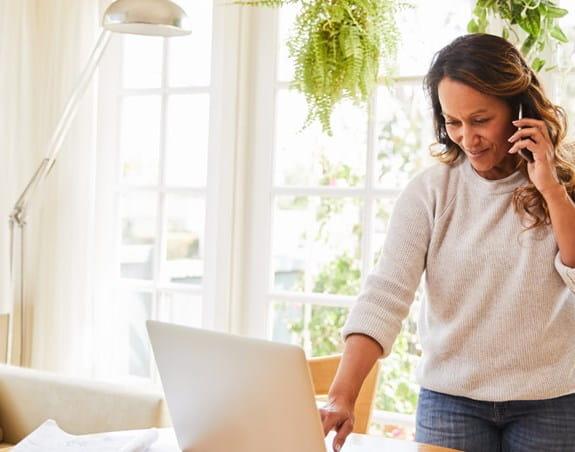 Une femme dans son salon, parlant au téléphone en regardant l'écran de son ordinateur portable.