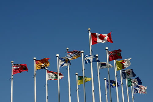 A collection of the Canadian and provincial flags waving on flagpoles