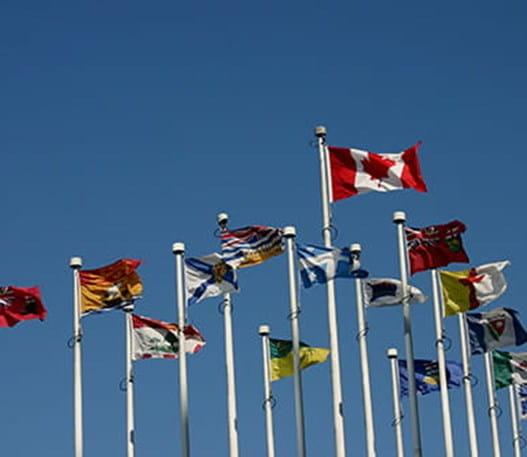 Drapeaux du Canada et des provinces flottant sur des mats.