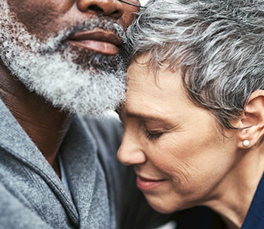 The face of a woman with short grey hair looking sad, hugging a man with a beard