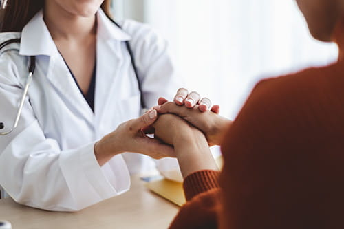 A doctor is embracing their patients hands while they are speaking with them