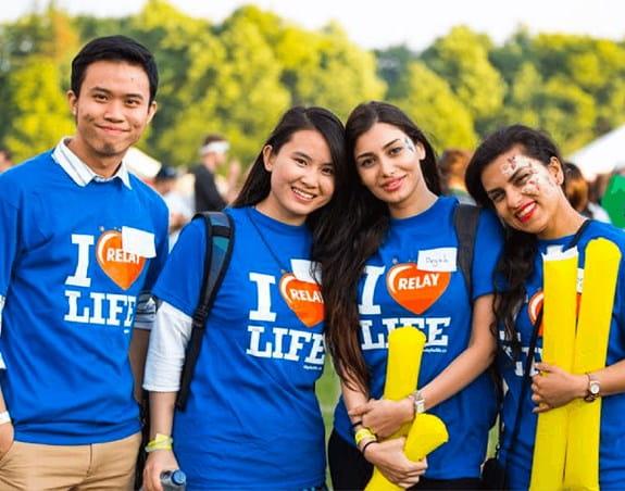 Un groupe d'amis, debout les uns près des autres, portant des t-shirts du Relais pour la vie et souriant