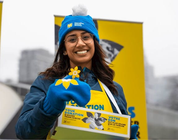 A volunteer smiles while holding up a daffodil pin while outside in winter clothes
