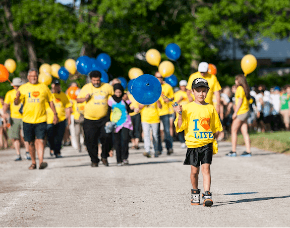 A young boy wearing a Relay for Life t-shirt walking around the track while holding a blue balloon