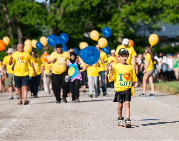 Un jeune garçon portant un t-shirt du Relais pour la vie, qui marche autour de la piste, un ballon bleu à la main
