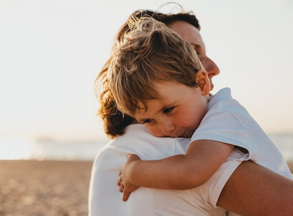 Young boy hugging his mom on the beach