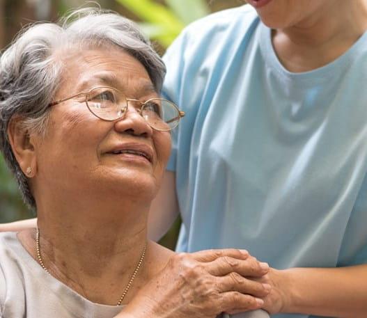 Dame âgée regardant vers le haut une personne ayant mis la main sur son épaule.