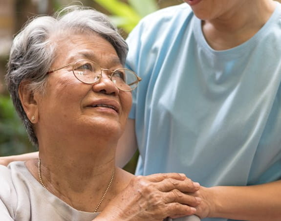 An older woman is looking up at someone who had placed their hand on her shoulder