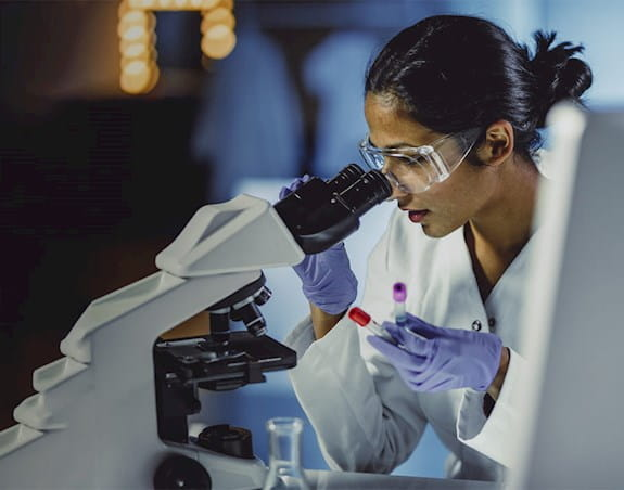 A female scientist in a lab looking into a microscope