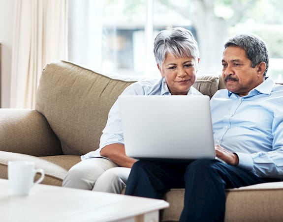 A couple on a couch looking at a laptop together