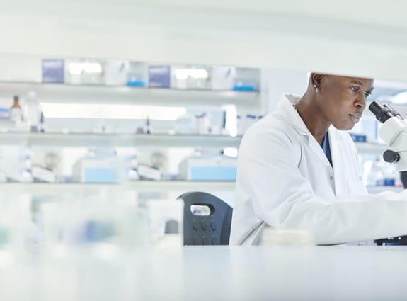 Une personne regardant sous un microscope dans un laboratoire