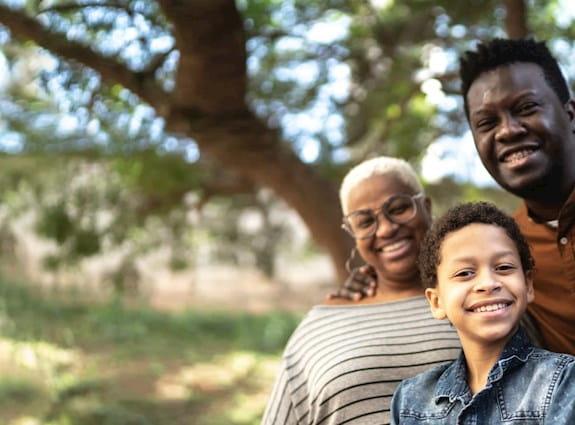 Trois adultes et un enfant souriant dehors
