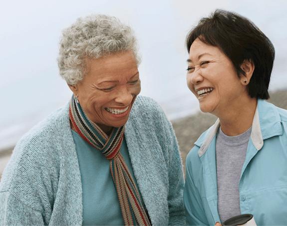 Deux dames âgées riant ensemble à la plage.