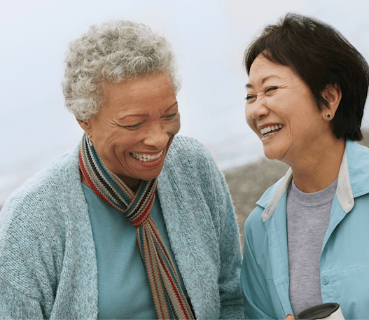 Two elderly women laugh with each other at the beach