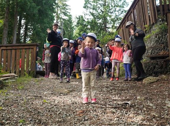 Groupe d'enfants dans un sentier, nous faisant un signe de la main.