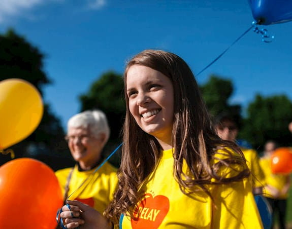 A woman wearing a relay for life shirt smiles while holding a balloon